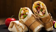 Burritos wraps with chicken, beans and vegetables on wood board
