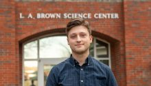 Brandon Bailey standing in front of the Brown Science Center