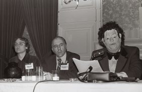 people at a table, one in a mask