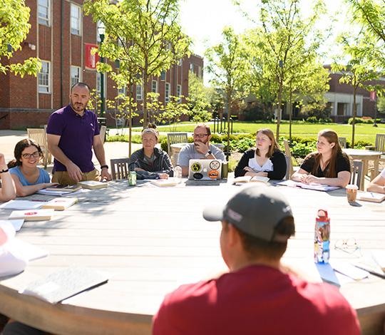 classes, such as this one being taught at an outdoor table, are a key component of academic life at transy