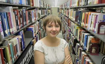 young woman standing amongst library bookshelves