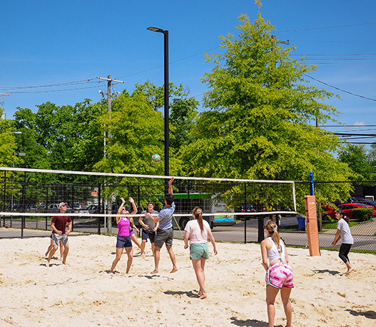 students playing volleyball on campus facilities