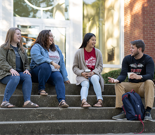 four students sitting on steps and talking