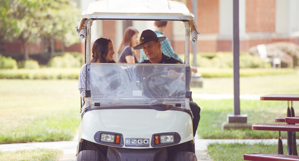 Public Safety officer and student in golf cart