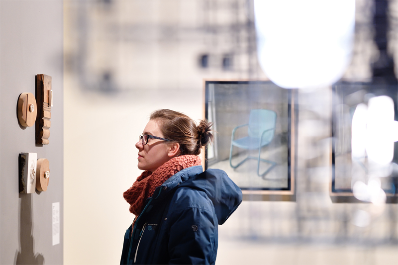 Woman looking at art hanging on the wall in a gallery