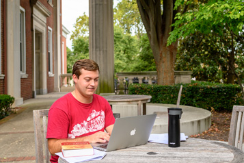 student outdoors, using a laptop to attend a virtual experience