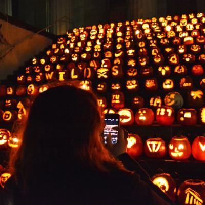 a woman taking a picture of illuminated pumpkins on the steps of Old Morrison